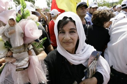 A Lebanese woman carries a statue of the